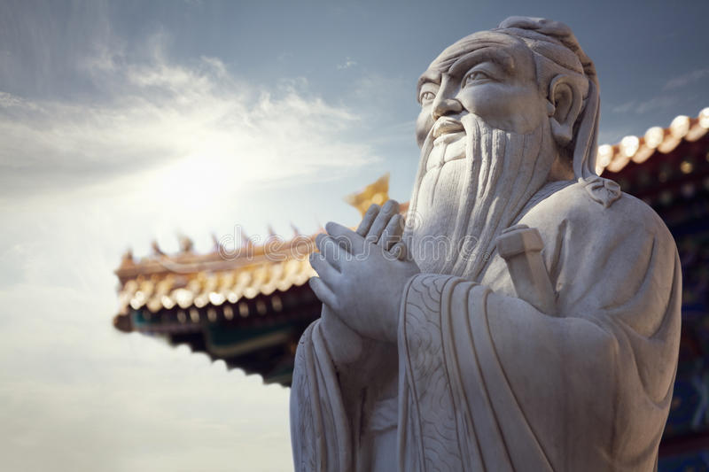 Close-up of stone statue of Confucius, pagoda roof in the background stock photos