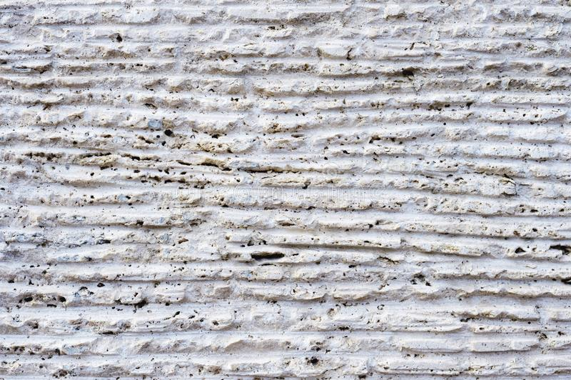 Close-up of stone surface with traces of processing. Parallel lines on the stone left by the cutting tool. Abstract. Textured background of white porous stone royalty free stock photos