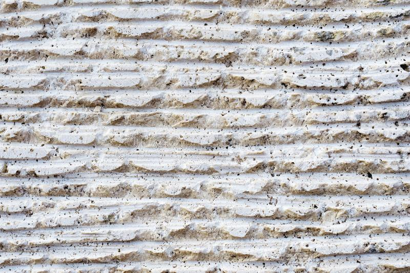 Close-up of stone surface with traces of processing. Parallel lines on the stone left by the cutting tool. Abstract. Textured background of white porous stone stock images