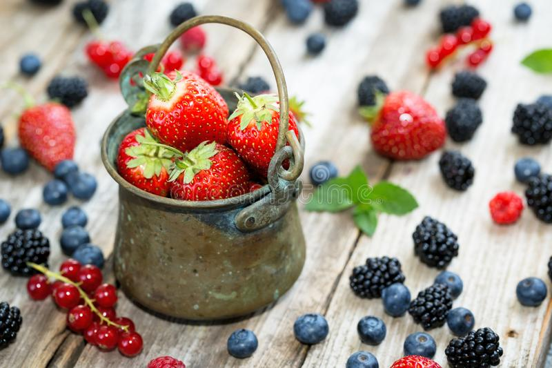 An antic pail on wooden table full with berries - strawberries, currants, blueberries. Close-up of strawberries in an antic pail on wooden table full with royalty free stock photo