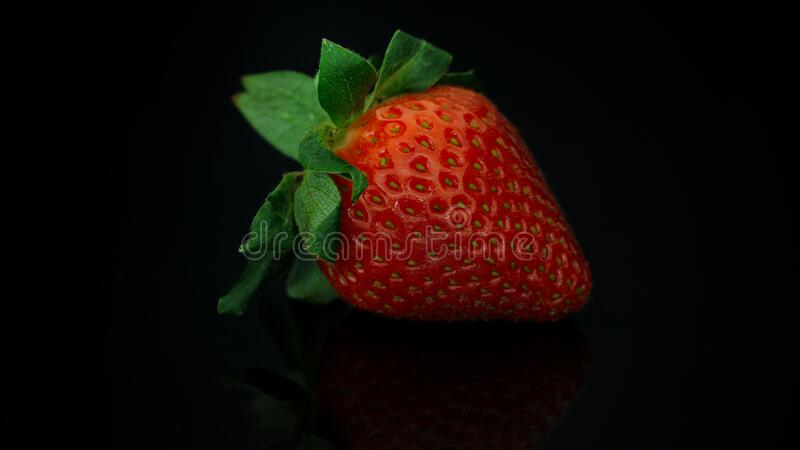 Close up strawberry in low light photography. Close up of strawberry in low light photography stock image