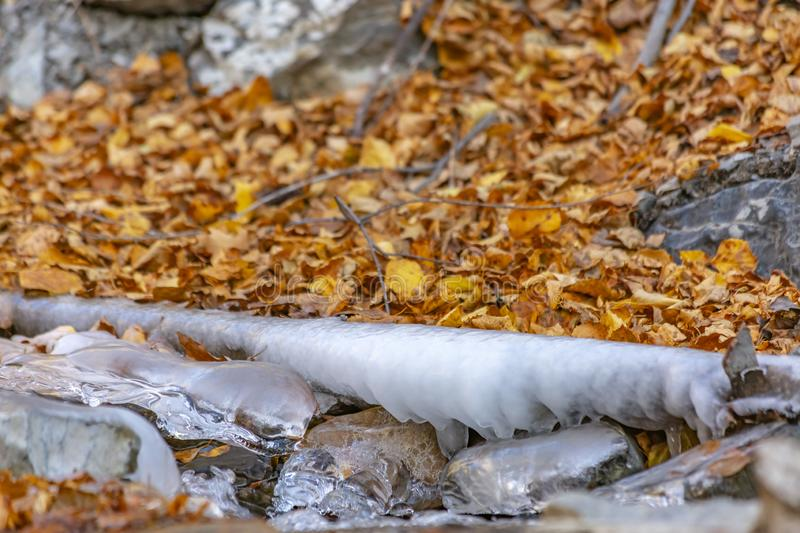 Close up of a stream with jagged rocks and translucent frozen water in winter stock image