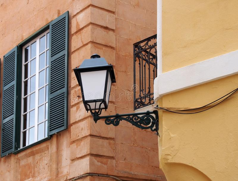 Street corner view of an ornate old street lamp mounted on a painted yellow house with iron balcony and window with open stock photos