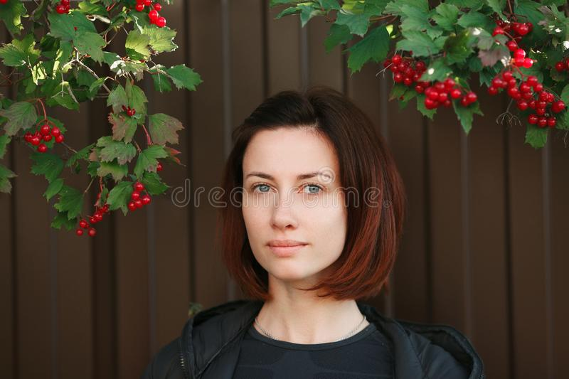 Close up street portrait of beautiful adult woman with gorgeous blue eyes looking at camera with slightly smile. Green leaves and royalty free stock image