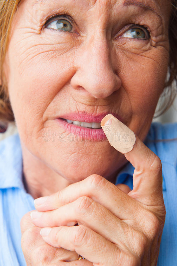 Close up stressed Woman band aid finger wound. Portrait mature woman in pain, hurt and suffering, close up of band aid on injured, cut bloody finger wound royalty free stock photos