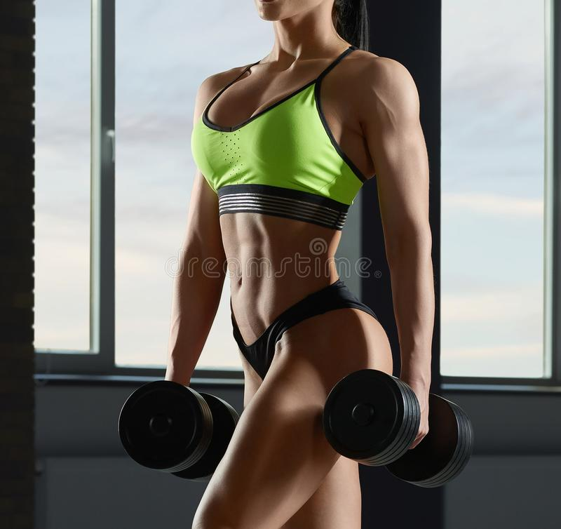 Close up of strong fit model`s body with muscles. Close up of strong fit model`s body with muscles doing fitness exercises with dumbbells. Having athletic royalty free stock images