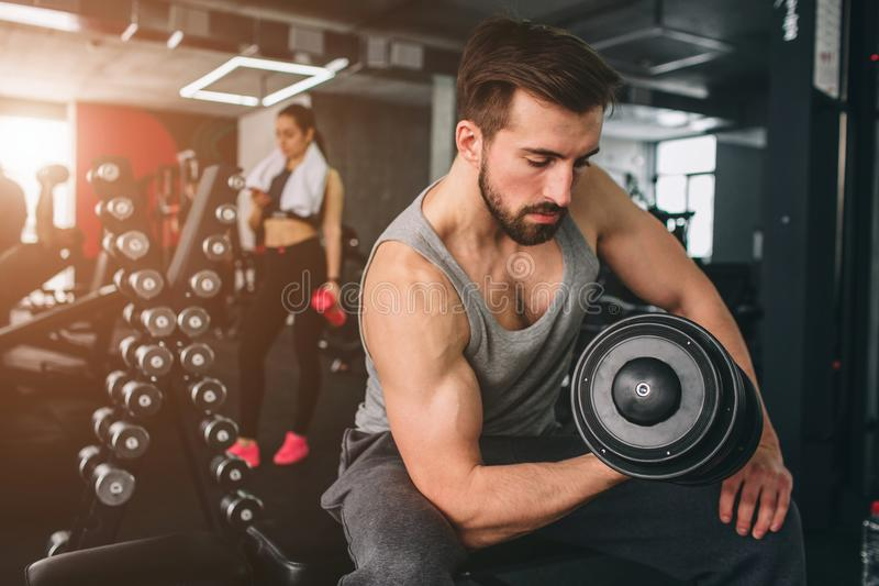Close up of strong guy that exercising with a dumbbell on the sport bench while hir girlfriend is standing nearby stock photos
