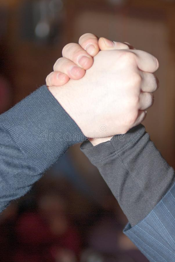 Close-up of a strong handshake of two men in a turtleneck and a suit. Close-up of a strong handshake of two men in a turtleneck and a dark-colored suit on a stock photos