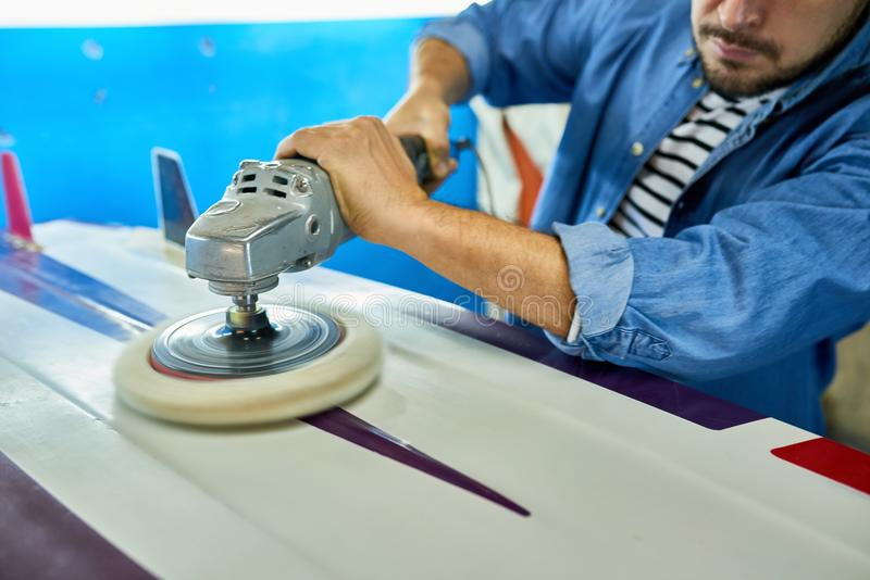 Tanned man polishing surfing board in workshop. Close up of strong male hands polishing new surfing board using electric polishing tool in yacht workshop, copy stock photo