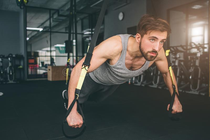 Close up of a strong and powerful man doing some stretching using trx loops for that. He is doing some pushups and stock photos