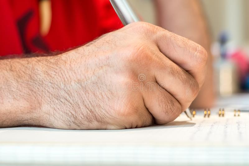 Close up of a student or businessman hand taking notes in his notebook with pen. royalty free stock photography