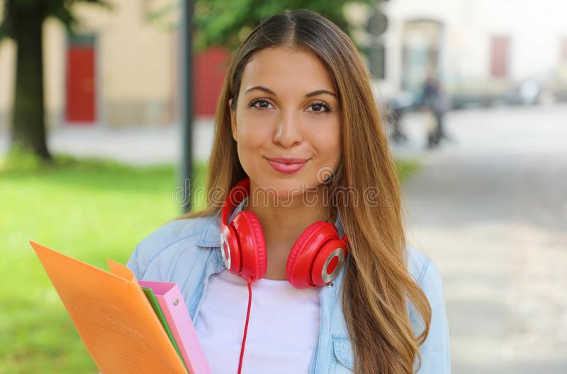 Close up of student girl with headphones holding folders outdoors.  royalty free stock photo