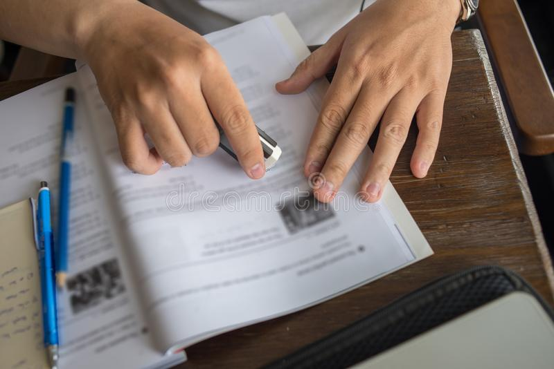 Close up of student hand using eraser on English workbook. Close up of student hand using eraser while doing homework royalty free stock photos