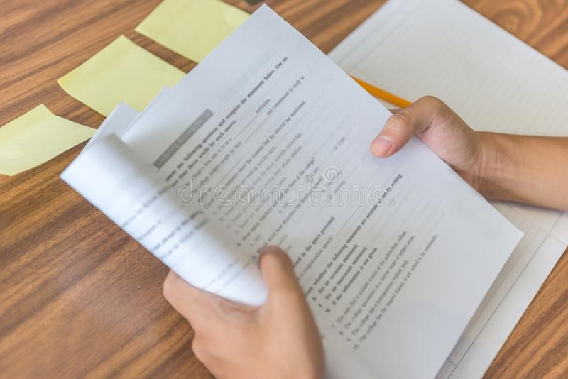 Student hands holding workbook and self studying. Close-up of student hands holding workbook and self studying royalty free stock photo