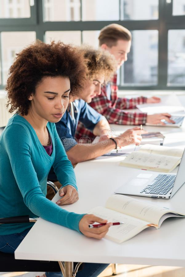 Close-up on student holding a pen over a book while studying royalty free stock photos