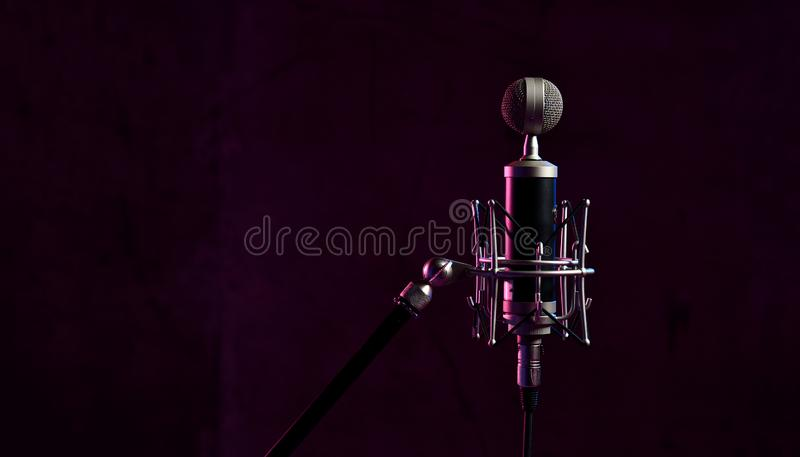 Close up studio condenser microphone with anti-vibration mount live recording neon blue and pink lights royalty free stock photography