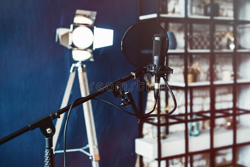 Close up studio condenser microphone with pop filter and anti-vibration mount live recording. Blue wall and decorative stock image