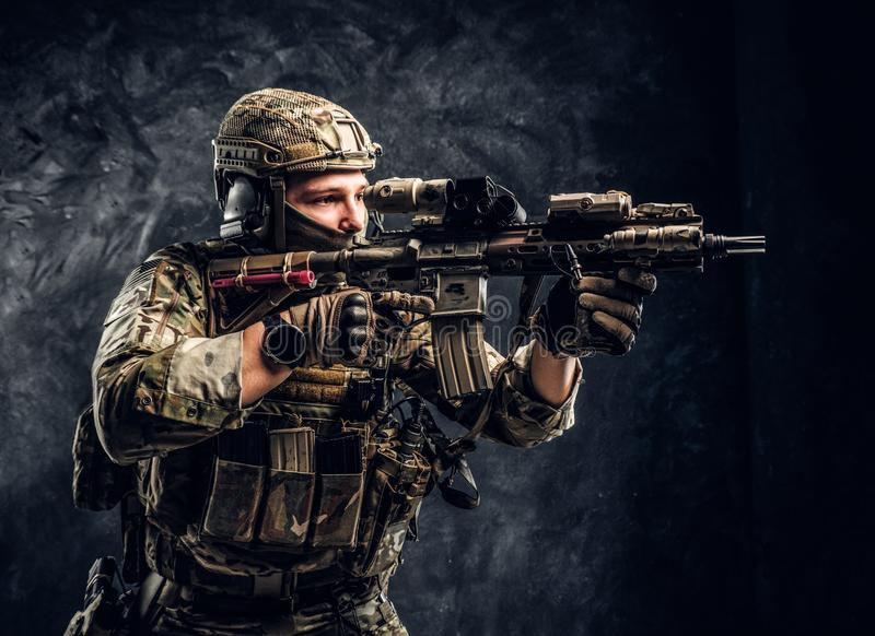 Close-up studio photo against a dark wall. The elite unit, special forces soldier in camouflage uniform holding an royalty free stock photo