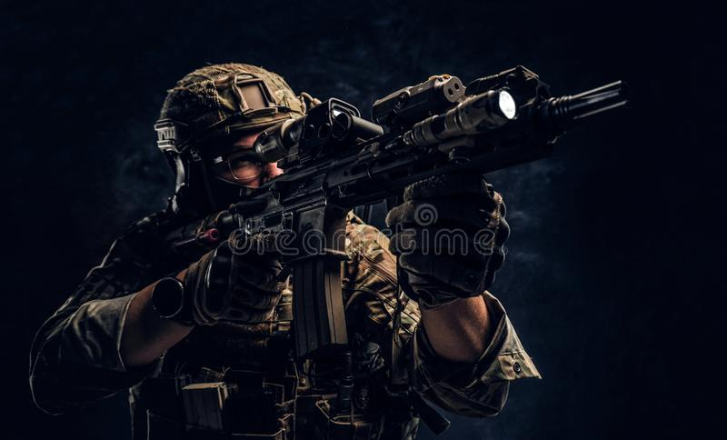 Close-up studio photo against a dark wall. The elite unit, special forces soldier in camouflage uniform holding an. Private security service contractors, the stock images