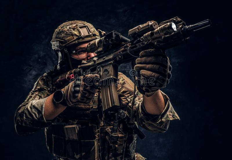 Close-up studio photo against a dark wall. The elite unit, special forces soldier in camouflage uniform holding an. Private security service contractors, the stock photos