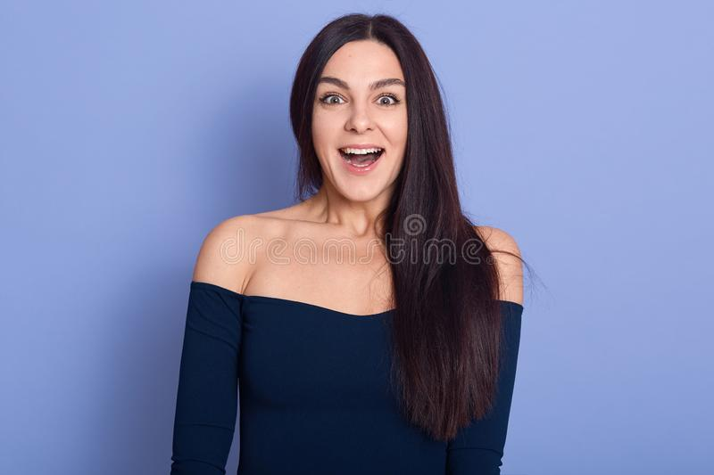 Close up studio photo of pretty charming cute female standing with open mouth, young smiling lady with long straight and bare stock image