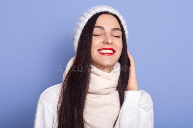 Close up studio picture of cheerful beautiful adorable brunette smiling sincerely, having attractive smile, closing eyes, enjoying royalty free stock photography