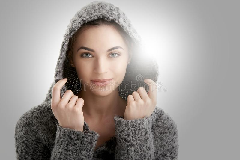 Close-up studio portrait of beautiful young woman wearing hoodie while posing at isolated white background royalty free stock photos