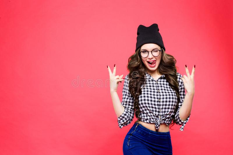 Close up studio portrait of cheerful blonde hipster girl going crazy making funny face and showing her tongue. Pink wall royalty free stock photo