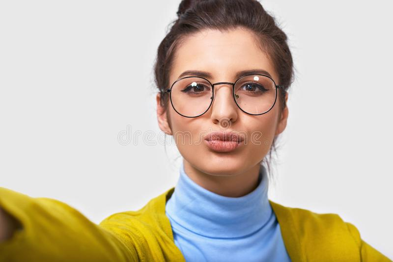 Close up studio portrait of cheerful pretty young brunette woman with beautiful clean skin, wears transparent eyeglasses royalty free stock image