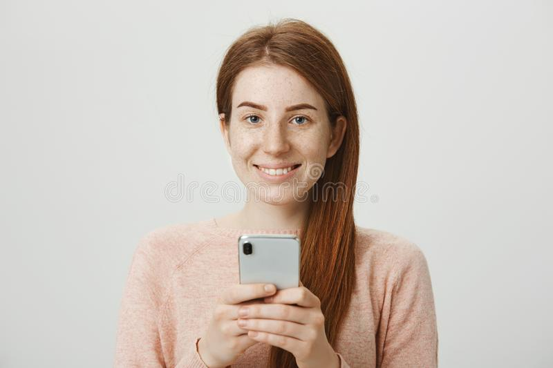 Close-up studio portrait of good-looking caucasian redhead girl holding smartphone and smiling broadly at camera while royalty free stock photos