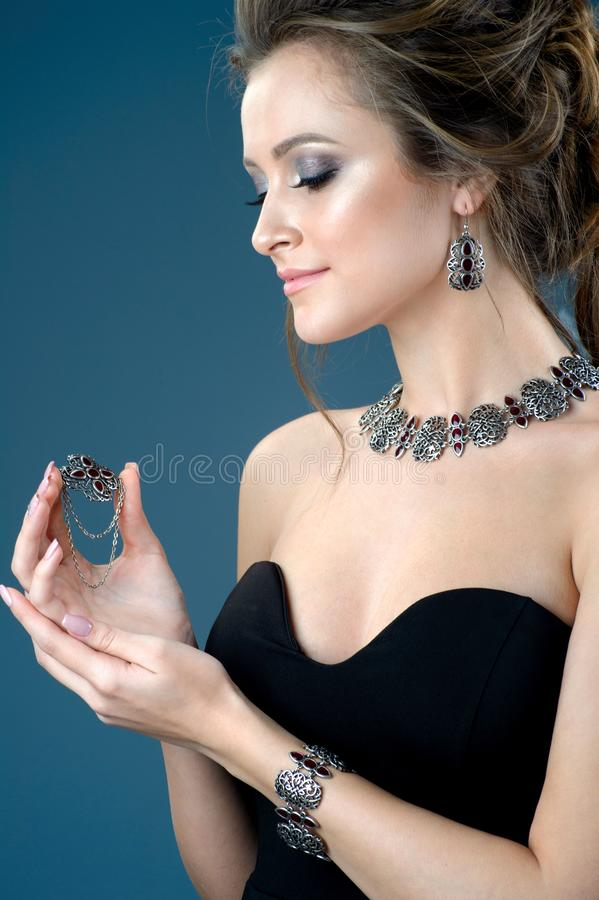 Close-up studio portrait model demonstrate stylish finger ring n. The close-up studio portrait model demonstrate stylish finger ring necklace and earring royalty free stock image