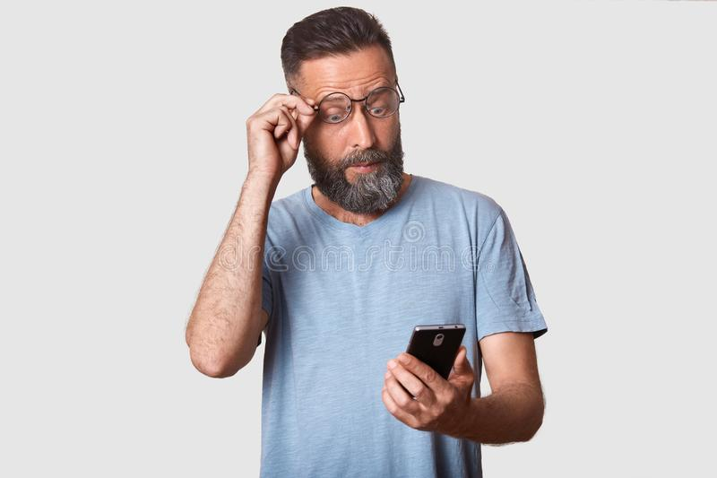 Close up studio portrait of slender bearded handsome curious man holding his smartphone in one hand, reading breaking news, royalty free stock photos