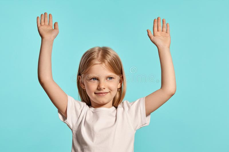 Close-up studio shot of a lovely blonde little girl in a white t-shirt posing against a blue background. stock image