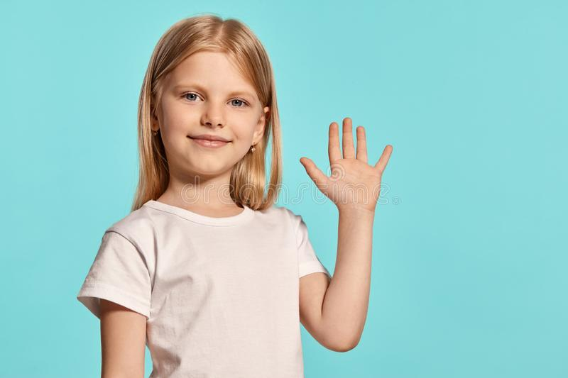 Close-up studio shot of a lovely blonde little girl in a white t-shirt posing against a blue background. royalty free stock photos