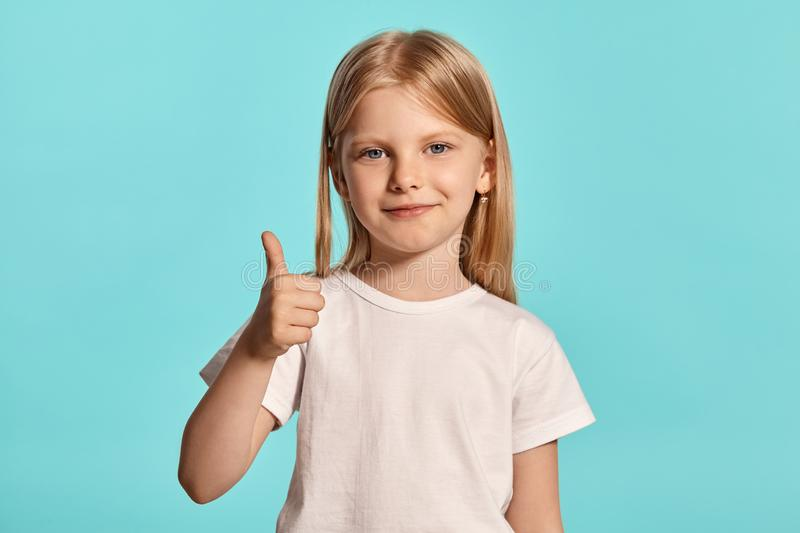 Close-up studio shot of a lovely blonde little girl in a white t-shirt posing against a blue background. royalty free stock photography