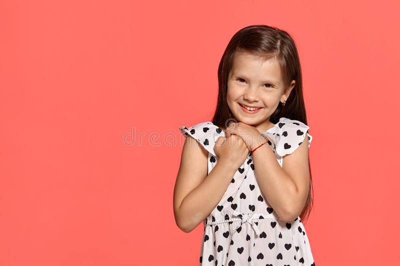 Close-up studio shot of beautiful brunette little girl posing against a pink background. stock photos