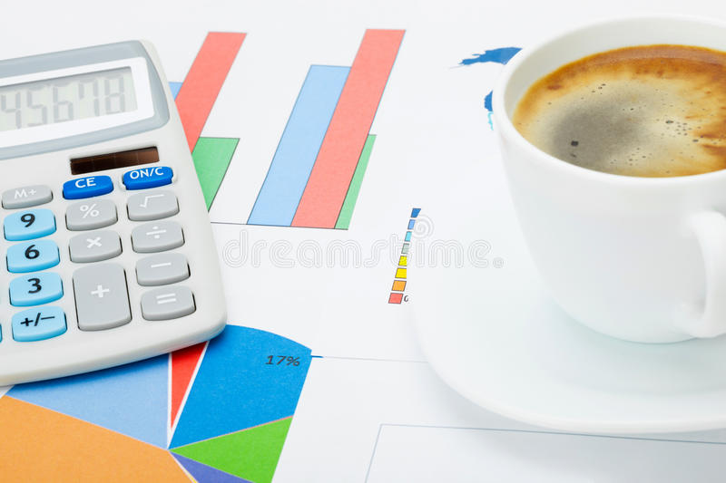 Close up studio shot of a coffee cup and a calculator over some financial documents royalty free stock image