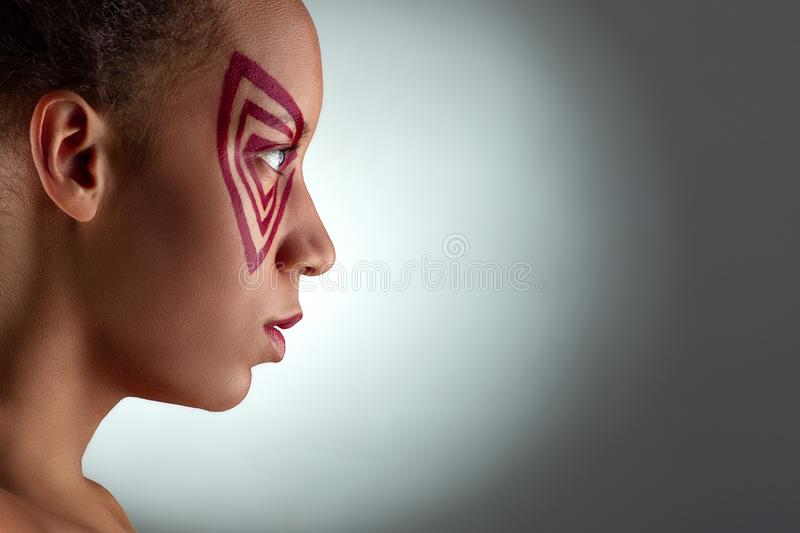 Close up studio shot of the woman of the mulatta with abstract make up on grey background with ligth, profile stock photos