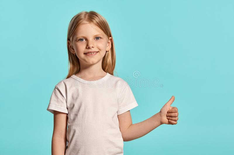Close-up studio shot of a lovely blonde little girl in a white t-shirt posing against a blue background. royalty free stock image