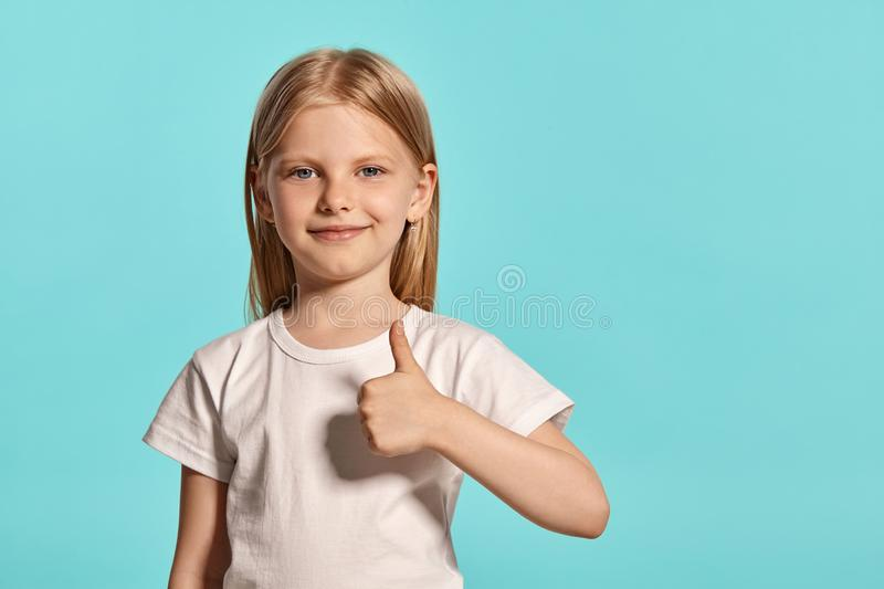 Close-up studio shot of a lovely blonde little girl in a white t-shirt posing against a blue background. stock photo