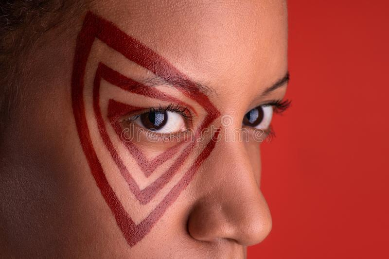 Close up studio shot of the young woman of the mulatta with abstract make up on coral background stock image