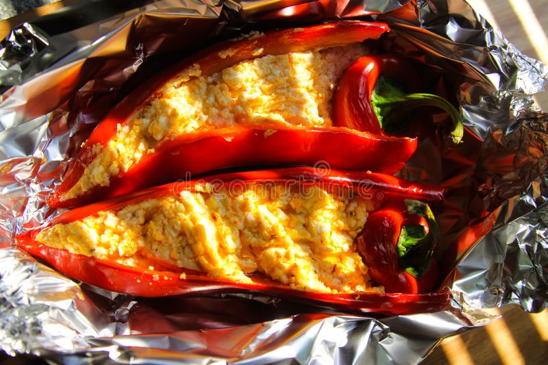 Close up of stuffed red paprika bell peppers with sheep feta cheese seasoned with spicy chili grilled in aluminium foil stock images
