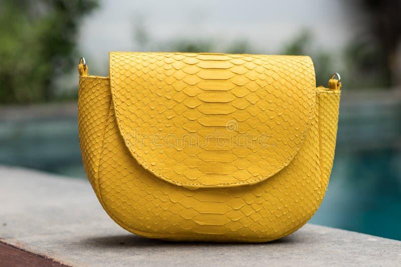 Close up of stylish female snakseskin python luxury bag outdoors. Fashionable and high style expensive female bag. Close up of stylish female snakseskin python stock photos