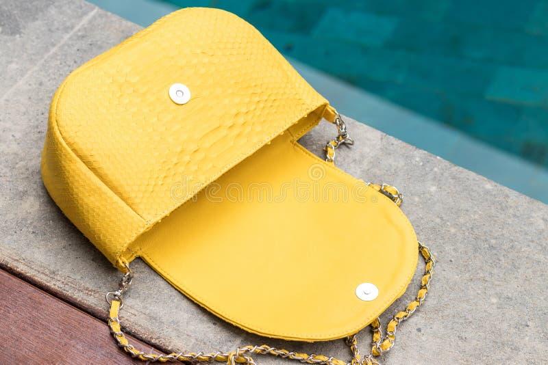 Close up of stylish female snakseskin python luxury bag outdoors. Fashionable and high style expensive female bag. Close up of stylish female snakseskin python royalty free stock image