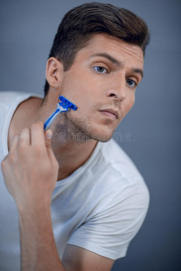 Close up. stylish modern guy shaves his face royalty free stock image