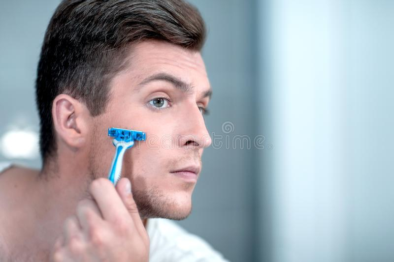 Close up. stylish young man shaves his face. royalty free stock images