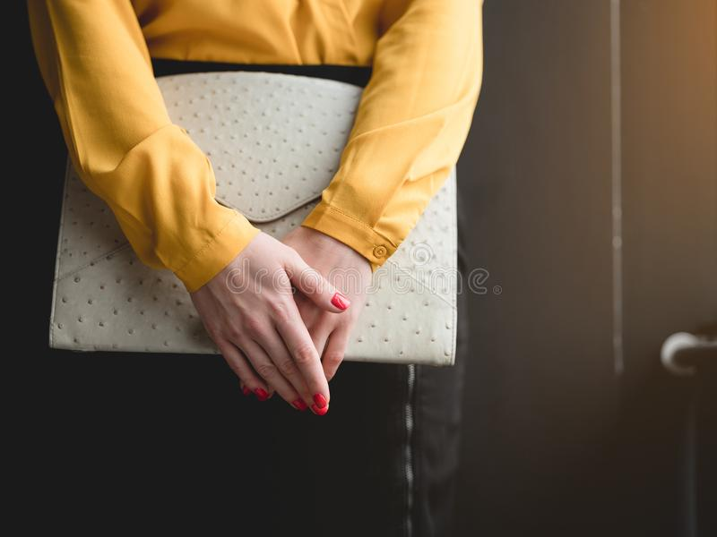 Fashionable businesswoman carrying trendy clutch stock photography