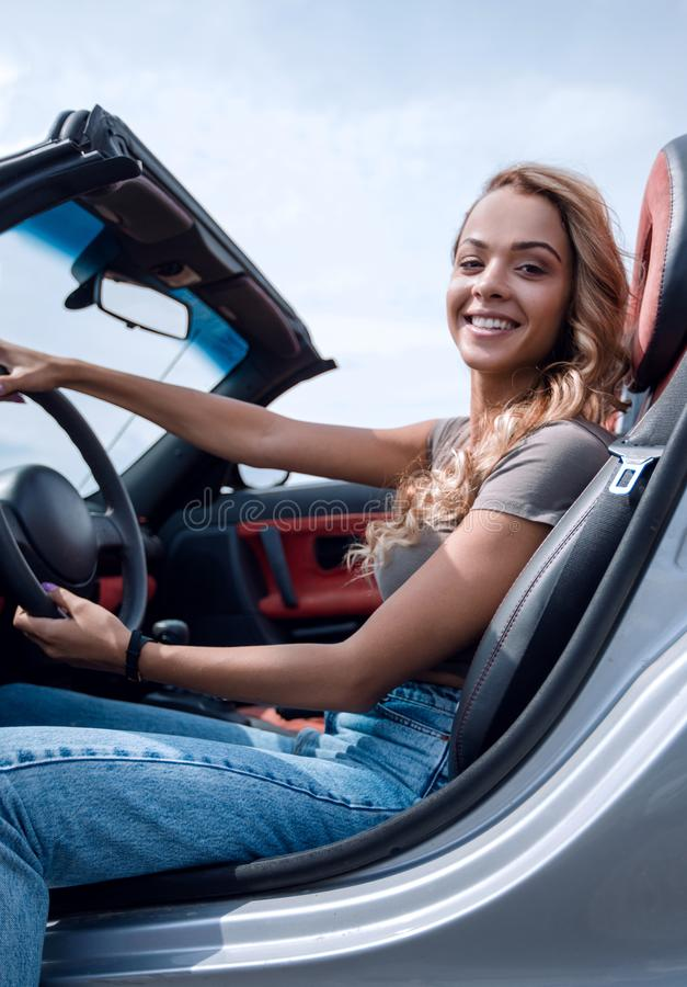 Close up.stylish young woman sitting in a luxury car royalty free stock photography