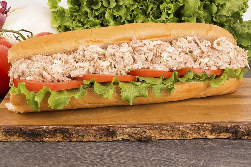 Close up of submarine tuna sandwich on wooden plank royalty free stock image