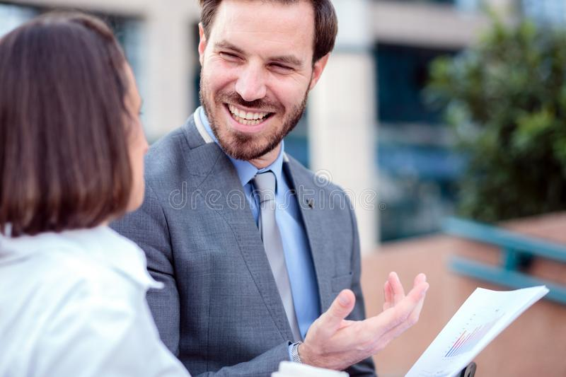 Close up of a successful happy young businessman talking with his coworker. And partner. Meeting in front of an office building, looking at sale report charts stock photo